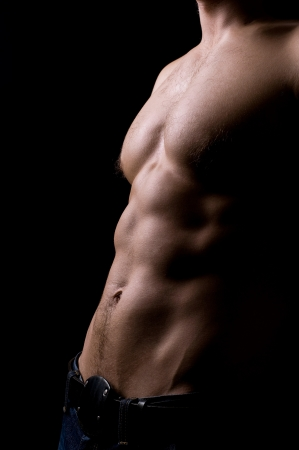 torso of strong athletic man on black