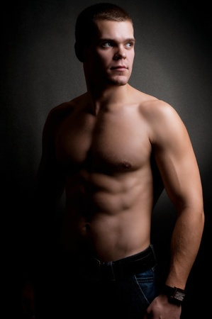 gay men: strong athletic man on black background