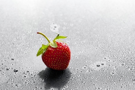 red strawberry with water drops over black