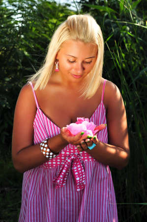 Young beautiful blonde girl with pink flower in hands