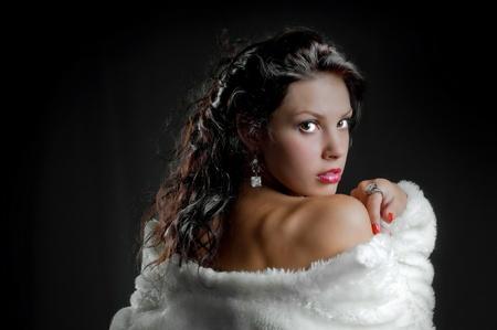 beautiful sexy girl in fur coat on black Stock Photo