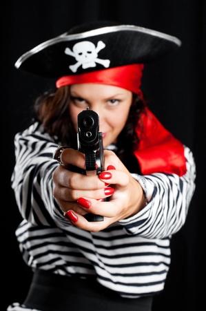 mujer pirata: Mujer joven vestido como un pirata en un sombrero negro sosteniendo una pistola Foto de archivo
