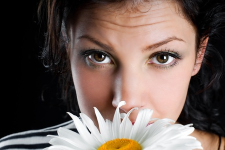 Beautiful young woman with chamomile in hand photo