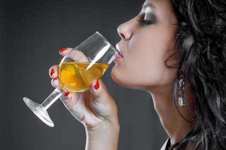 Beautiful girl drink wine on black