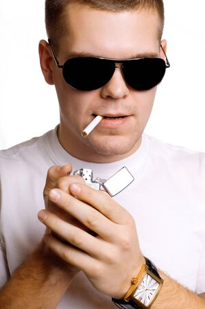 sexy strong man in sunglasses lighting his cigarette isolated on white Stock Photo - 13304497