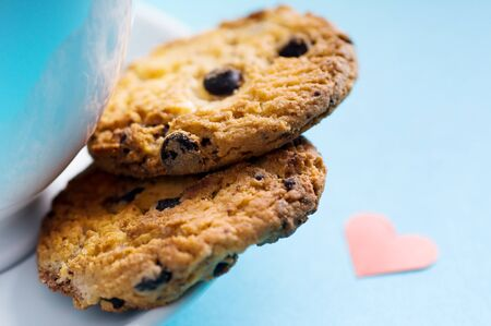 Chocolate homemade pastry biscuits on blue background with heart