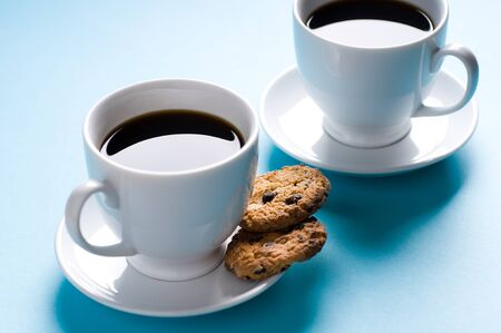 Two coffee cups with cookies on blue background