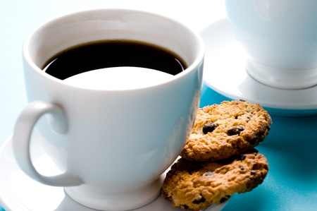 Two coffee cups with cookies on blue background photo