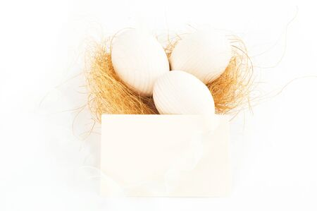 decorative eggs lying on some hay with white ribbon and card Stock Photo - 12815682