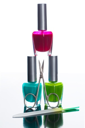 Nail polish bottles pyramid with scissors on gloss background