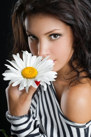 Beautiful young woman with chamomile in hand Stock Photo - 13304516