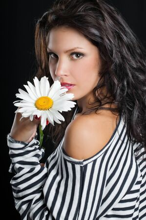 Beautiful young woman with chamomile in hand