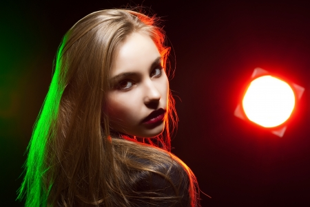 Beautiful girl posing in front of shining colored creative lighting background Stock Photo - 15531558