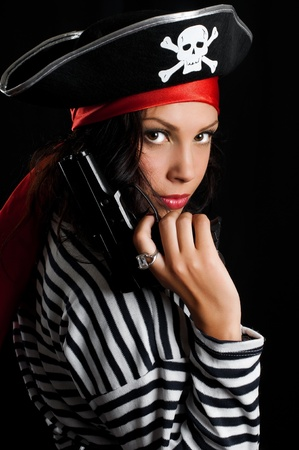 Young woman dressed as a pirate in a black hat holding an gun