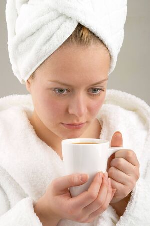 The girl with a cup of coffee in a dressing gown photo