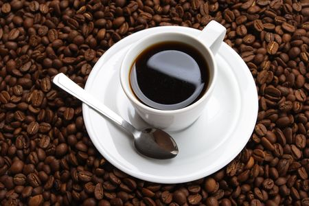 Cup with coffee, costing on coffee grain photo