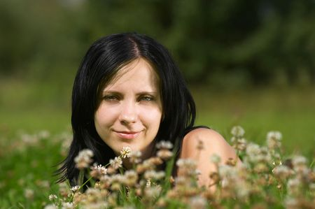 The girl lays in a grass and flowers photo