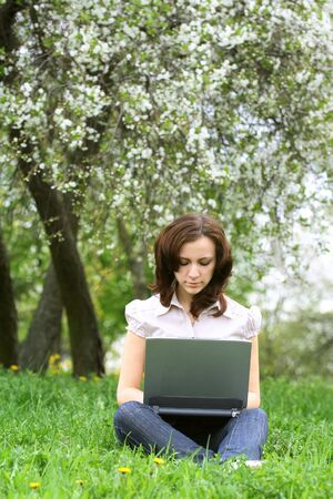 The girl with laptop on the nature photo