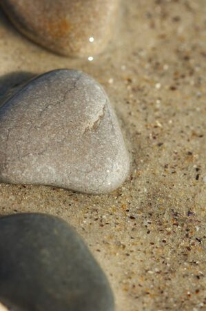 Stones on sand at the sea, a pebble photo
