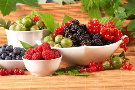 profiting: Berries in plates, on a table, among green leaves Stock Photo