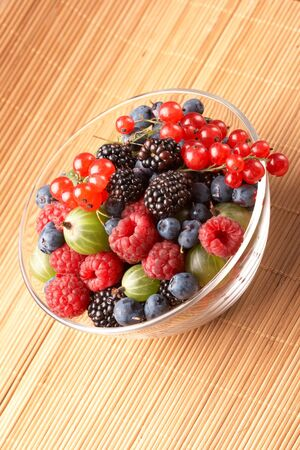Fruit mix in the glass container, on a table from straw photo