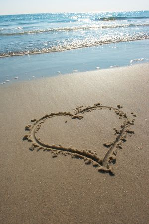 Heart drawn on sand, seacoast photo