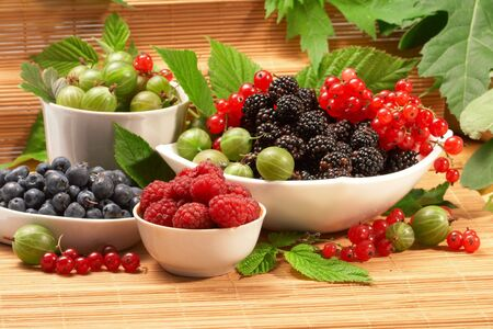 Berries in plates, on a table, among green leaves photo