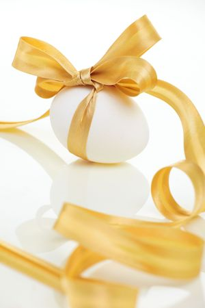 Easter egg with a bow golden photo