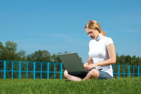 The girl with laptop on a green lawn photo