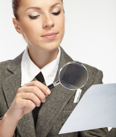 woman holding a magnifying glass in the hand photo