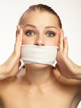 oppressed: Cute young woman with white band on the mouth Stock Photo