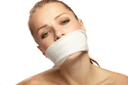 oppress: Cute young woman with white band on the mouth Stock Photo