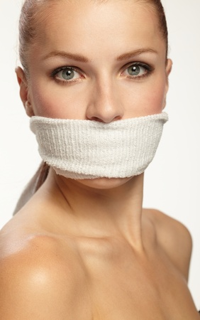 hostage: Cute young woman with white band on the mouth Stock Photo