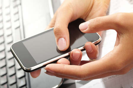 databank: Using a PDA mobile phone with laptop keyboard background,  Stock Photo