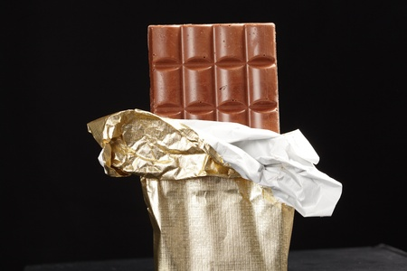 snack bar: chocolate in bar with open gold cover.