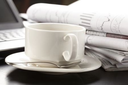 Cup of fragrant coffee on a morning paper business news photo
