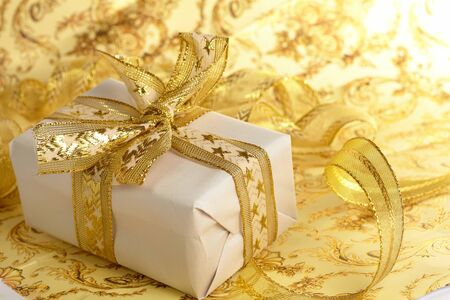 Beautiful gift box on the gold background photo