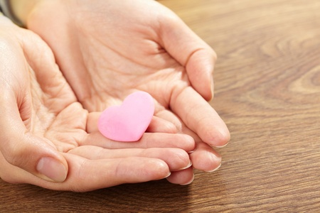 Woman holding pink heart in the hand  photo