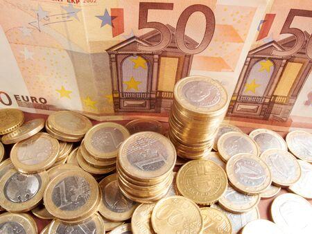 dinero euros: Las monedas en euros en fondo de dinero de billetes