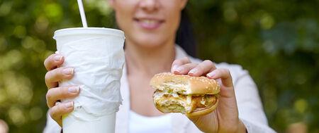 woman eating hamburger and cocktail photo
