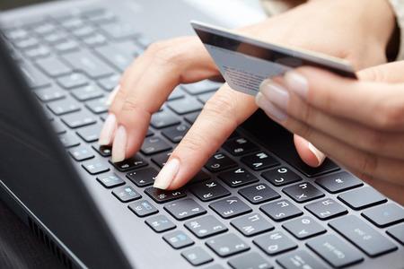 comprando: Mujer que sostiene la tarjeta de cr�dito en la computadora port�til para concep compras en l�nea