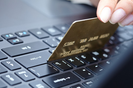 woman holding credit card on laptop for online shopping concep photo