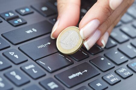 poverty relief: coin on laptop Stock Photo