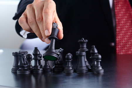 strategic: businessman playing chess game