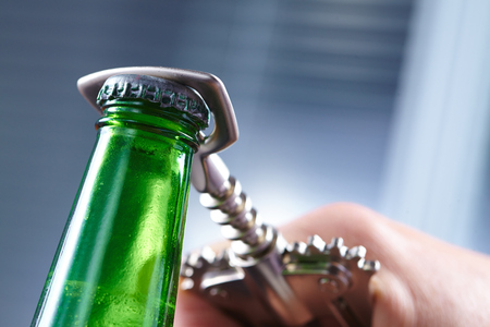 glass beer bottle: A hand opening a bottle of beer