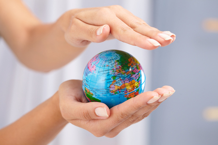 woman's hand: womans hand with globe Stock Photo