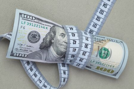 twining: dollars with measuring tape Stock Photo