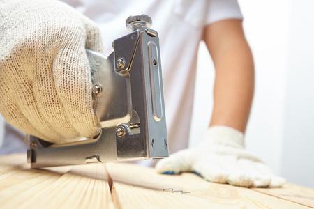installer: Male installer using stapler for wooden plank