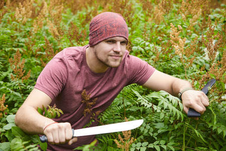 flatfoot: A man with a machete making his way through a thicket, sailor pirate in the jungle Stock Photo