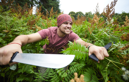 A man with a machete making his way through a thicket, sailor pirate in the jungle Stock Photo